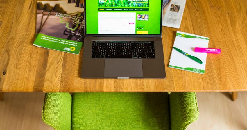 Schreibtisch mit Schreibmaterial, Laptop und leerem Stuhl davor.